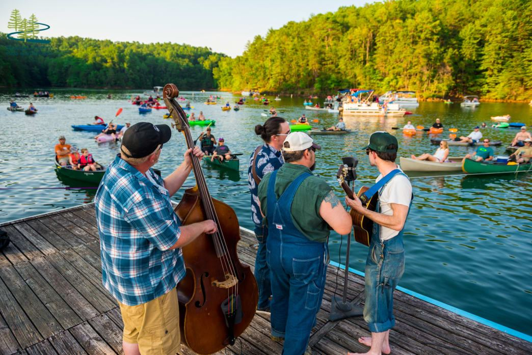 Musicians playing music on a dock by Philpott Lake